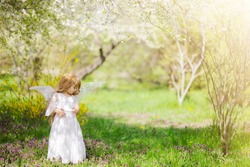 Fairy tale consept. Little toddler girl wearing beautiful princess dress with fairy wings in the forest or park, spring day, white blooming trees