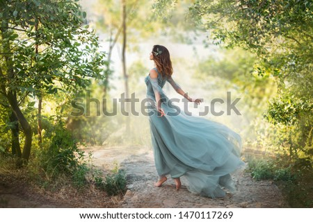 Photo of  fairy-tale princess in light summer blue turquoise dress on wide path and walks towards wind, graceful dancing girl in image of flower with flying long hem of dress, nymph of bright green forest