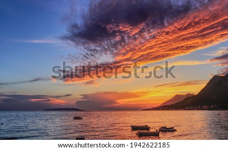 Fairy-tale sunset setting over the foot of the mountain. The sun reflects off the surface of the Mediterranean Sea and illuminates small boats that swim in an indefinite direction. Gradac, Makarska Stock fotó ©