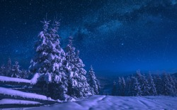 Fairytale carpathian frozen highlands covered with snow. Night starry sky with milky way. Winter time. Ukraine, Europe.
