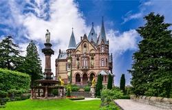 Fairytale castle with a fountain. Castle entrance. Fairy tale castle view. Castle with fountain in park