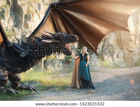 fairytale girl queen blonde white hair aqua blue color clothes stands rocks, strong powerful awesome black dragon, myth animal large wings, sun glare. creative art fantasy cape suit outfit gown image