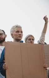 Faith. Group of activists giving slogans in a rally. Caucasian men and women marching together in a protest in the city. Look angry, hopeful, confident. Blank banners for your design or ad.