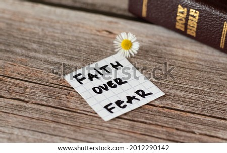 Faith over fear. Inspiring handwritten quote from the Bible Book. Trust, faith, hope, belief in God and Jesus Christ. Devoted faithful Christian biblical concept. A closeup.