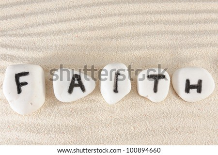 Faith word on group of stones with sand as background