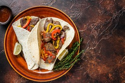 Fajitas Tortilla wraps with beef meat steak stripes, sweet pepper and onions. Dark Wooden background. Top view. Copy space