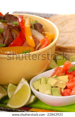 Fajitas with tortillas, tomatoes, guacamole and limes