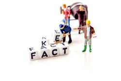 fake and fact text formed of white dices with black letters and little miniature figurines of workers on white background, distinguish between credible information and fake news, critical thinking