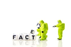 fake and fact text formed of white dices with black letters and little miniature figurines of workers, how can you distinguish between credible information and fake news, critical thinking