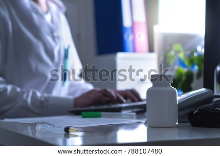 Fake doctor, quack or charlatan in hospital office. Medical crime, illegal health care, insurance fraud, negligence, treatment error or malpractice. Man in dark hospital typing computer prescription.
