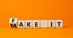 Fake it until you make it symbol. Turned a cube and changed words 'fake it' to 'make it'. Beautiful orange background. Business, and fake it till you make it concept. Copy space.