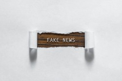 Fake News - an inscription in a torn white paper. The concept of false information, manipulation, propaganda.