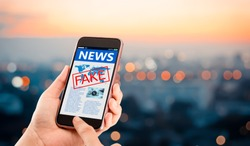 Fake news,Hoax concept.Hands holding mobile phone on blurred night city as background