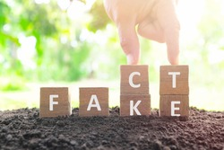Fake news versus facts concept. Hand changing fake wooden blocks to word fact in natural background.