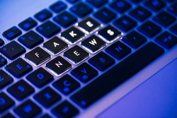 Fake news written on a backlit laptop keyboard close-up with selective focus in a blue ambiant light
