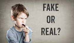 Fake or real, Boy considering the question, on grunge background, writing and thinking, copy space