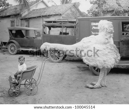 Fake ostrich pushing boy in stroller