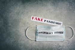 Fake pandemic. Conspiracy theory. Text on a gray vintage background. Vignette. Disposable surgical mask.