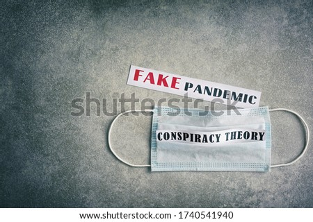 Fake pandemic. Conspiracy theory. Text on a gray vintage background. Vignette. Disposable surgical mask. ストックフォト ©