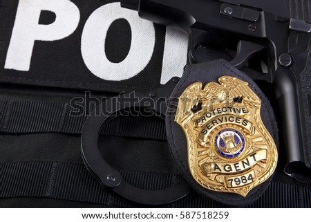 Fake prop badge designed by photographer on wood with firearm and bullets. Badge number is also fake.  Macro shot with focus on the word agent.   #587518259