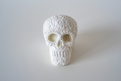 Fake white painted decorative carved skull with florals on a white background, decoration, DIY project, Halloween,  Day of the Dead
