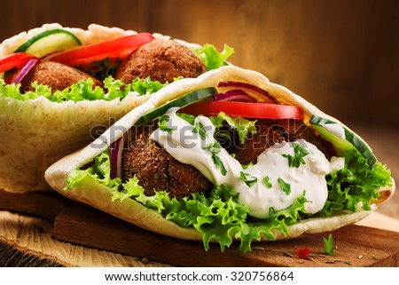 Falafel and fresh vegetables in pita bread on wooden table Stockfoto ©