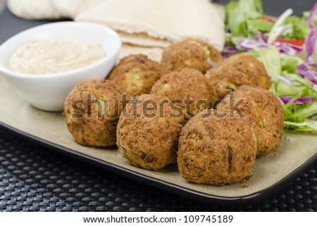 Falafel - Deep fried chickpeas balls served with tahini, salad and pitta bread.