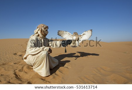 Shutterstock Falconer training a desert owl (strix adorami) in a desert near Dubai