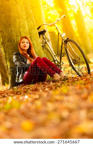 Fall active lifestyle concept,. Beauty young redhaired woman fashion girl relaxing in autumn park with bicycle, sitting alone under tree, outdoor