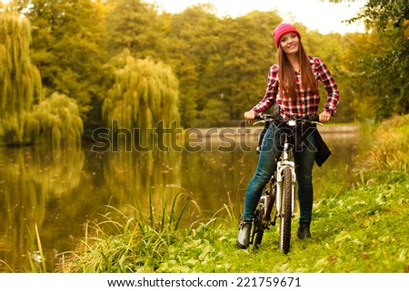 Fall active lifestyle concept,. young woman sporty casual girl relaxing in autumnal park with bicycle, outdoor