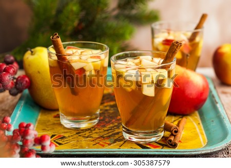 Fall and winter  drink with apples,pears and cinnamon in glasses on the vintage tray
