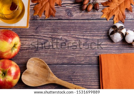 Fall / Autumn decorated and themed background on a wooden rustic table. Decorated with apple juice, apples, cotton, leaves, wooden spoon, and orange towel. Shot from above with free space for words. #1531699889