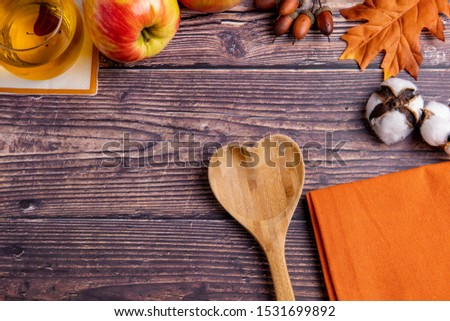 Fall / Autumn decorated and themed background on a wooden rustic table. Decorated with apple juice, apples, cotton, leaves, wooden spoon, and orange towel. Shot from above with free space for words. #1531699892