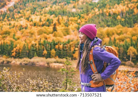 Fall autumn hiker girl outdoor at nature forest lake with backpack for camping travel trip. Happy Asian woman hiking outdoors with bag and hat, cold outerwear gear. - Shutterstock ID 713507521