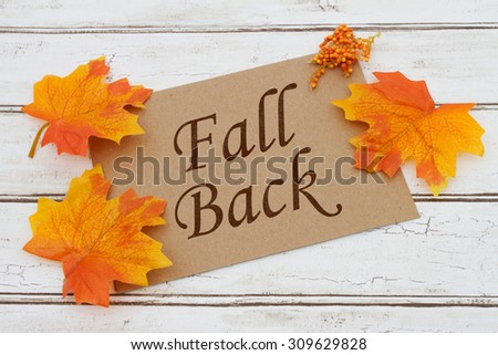 Fall Back  Card, A brown card with words Fall Back  over a distressed wood background with Autumn Leaves