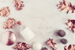 Fall beauty products flatlay on white marble table. Rose gold leaves, coconut oil, candles. Copyspace