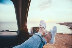 Fall car trip in sunset. Freedom travel concept. Spending weekend in roadtrip. Woman feet on car window, watching the sea.