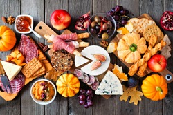 Fall charcuterie table scene against a dark wood background. Assorted cheese and meat appetizers. Top down view.