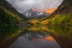 Fall color of aspen forest at Maroon Bells, Colorado. Beautiful sunrise with reflection lake.