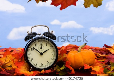 Fall colored leaves with a black clock on a sky background, Fall Leaves