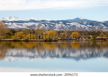 Fall colors against the snow capped mountains and reflection of both in the lake in the foreground.  Focus is on horizon line.