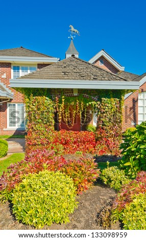 Fall colors. House entrance with ivy around the columns Landscape design.