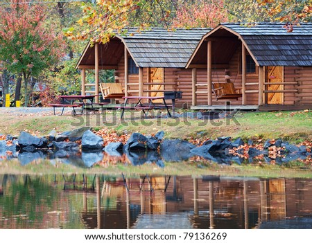 Fall colors of the trees and a cabin reflecting in the water of a small lake in North Carolina, USA.