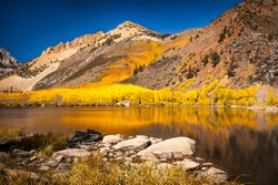 Fall colors on a mountainside reflect on a quiet lake in the Owens Valley.
