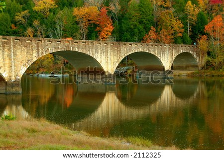 Fall colors surround a historic bridge, reflected in the Cumberland River just upstream of the Cumberland Falls in Kentucky, USA.