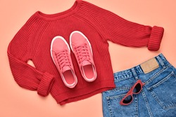 Fall fashion Flat lay. Trendy red jumper, Stylish hipster sneakers, sunglasses, denim. Creative Woman Clothes Accessories layout.Fall Girl fashionable Outfit, autumnal orange pastel color