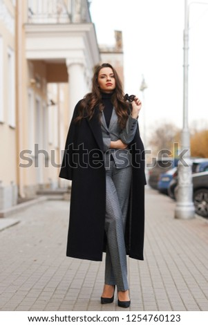 Fall fashion look. Stylish woman in gray suit and black coat standing alone at city street in old town and looking in camera. Elegant lady full length portrait