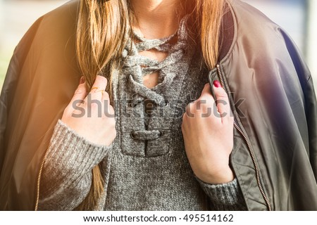 fall fashion outfit detail. woman in an autumn fashion outfit, stylish bomber jacket and grey wool sweater. warm instagram grade
