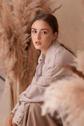Fall fashion portrait. Brunette girl with pony tail and natural makeup. Elegant woman posing between ears of rye at textile background. Stylish female model in brown skirt anf beige jacket