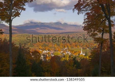 Fall foliage landscape overlooking Stowe Community Church and Stowe Village in the foreground, Stowe, Vermont, USA